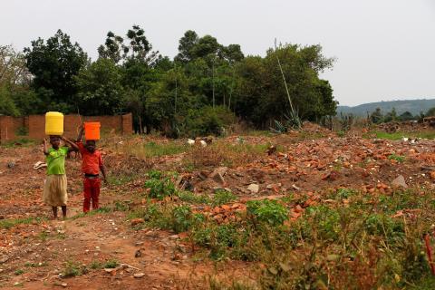To barn bærer vann i ruinene like utenfor ABGs gullgruve. Husene er jevnet med jorden, slik at gruven skal kunne utvides. Foto: Kenneth Lia Solberg